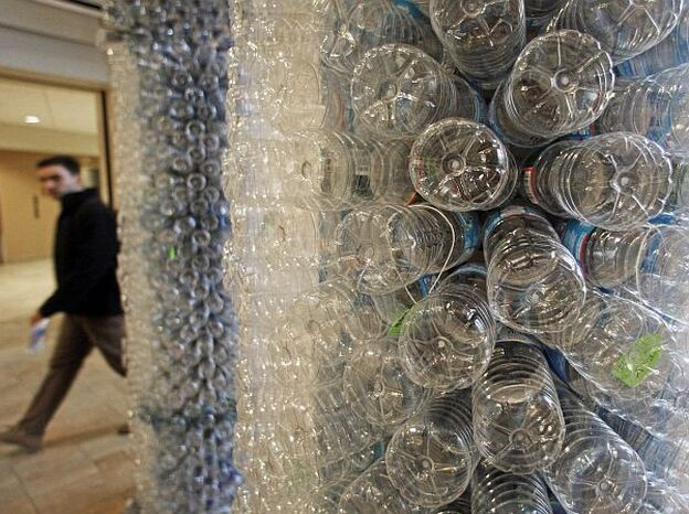 A student walks past a sculpture made of empty water bottles on the University of Vermont campus. UVM has banned the sale of bottled water.