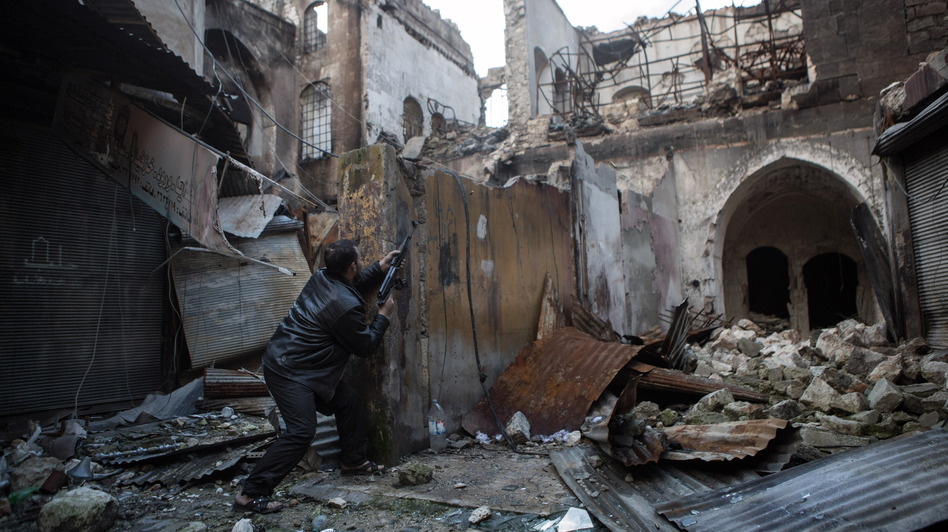 A rebel fighter fires toward Syrian government forces in the Bab al-Nasr district of Aleppo's Old City, earlier this month. The city has been a major battleground for the past six months. (AFP/Getty Images)