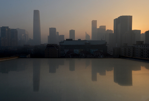 Air pollution hangs over the skyline as the sun rises over the central business district in Beijing on Monday. Dense smog has shrouded the city with pollution at hazardous levels for days, and residents were advised to stay indoors.