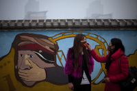 A woman helps adjust a mask for her friend outside an amusement park on a hazy day in Beijing on Saturday.