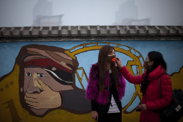A woman helps adjust a mask for her friend outside an amusement park on a hazy day in Beijing on Saturday. (AP)