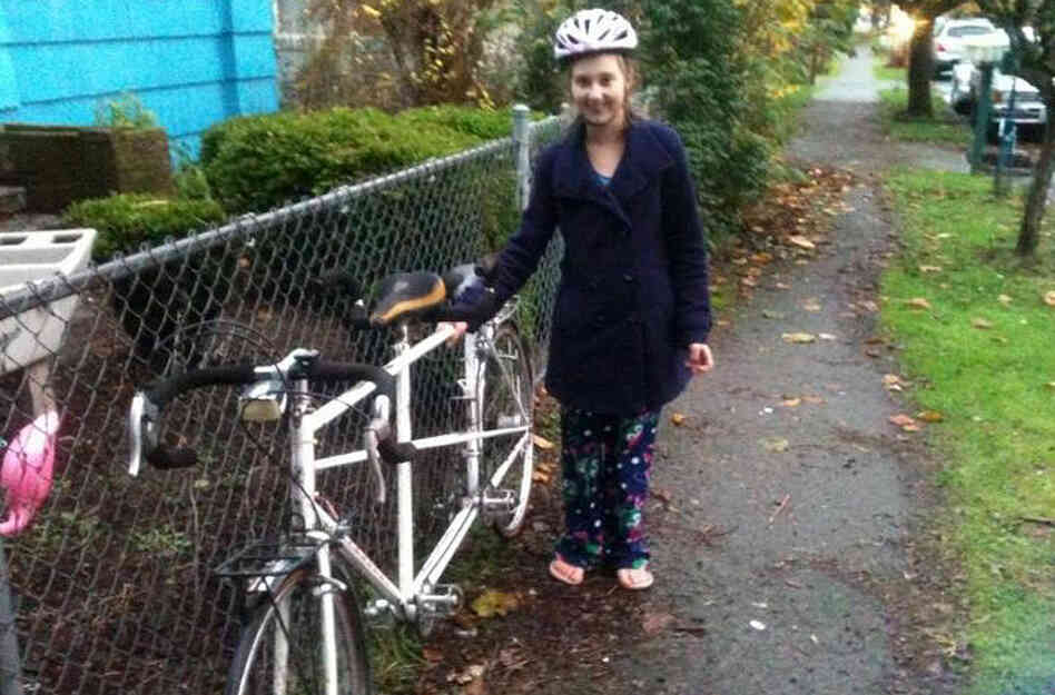Courtney Forbes, 21, stands with the tandem bicycle that she and her husband, Harly relied on for transportation before it was s