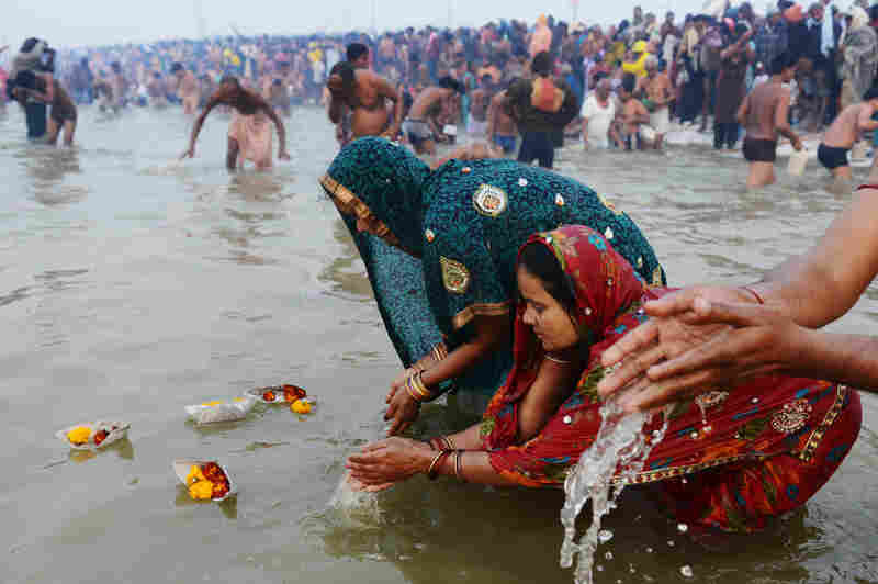 Pilgrims release offerings in the river's current while bathing.