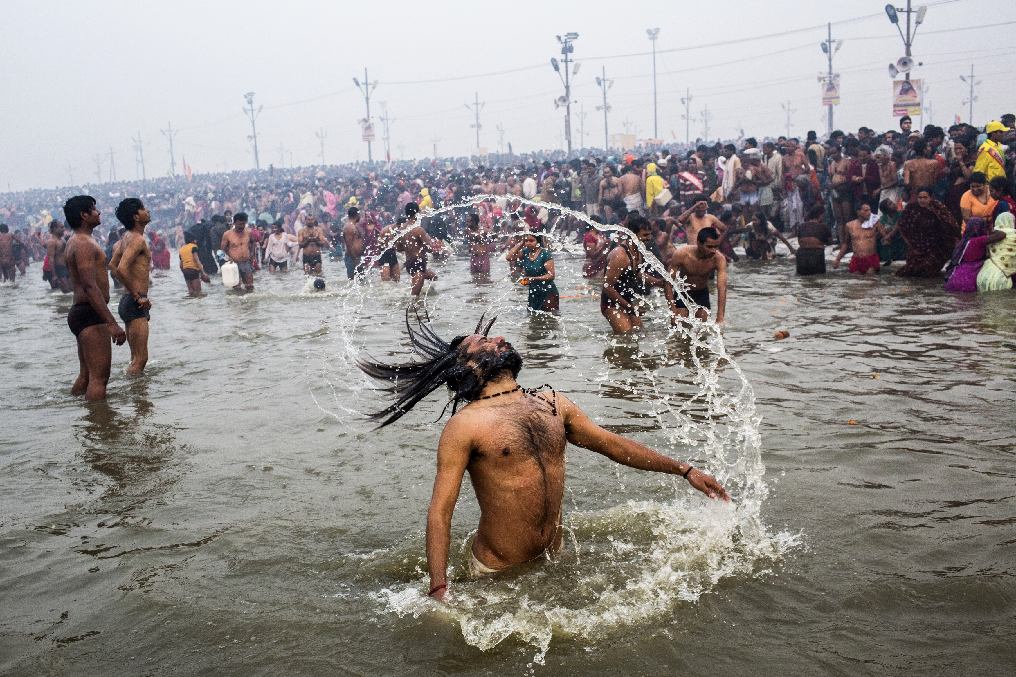 A Hindu holy man, or Naga Sadhu, swings his hair during the royal bath on Makar Sankranti.