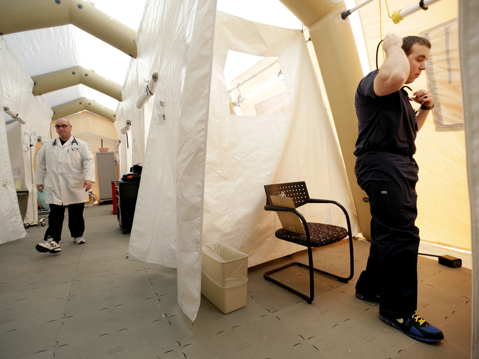 Physician assistants Scott Fillman (left) and Andrew Hunadi get ready to see patients with flu symptoms, in a tent erected just outside the emergency entrance at the Lehigh Valley Hospital in Allentown, Pa.
