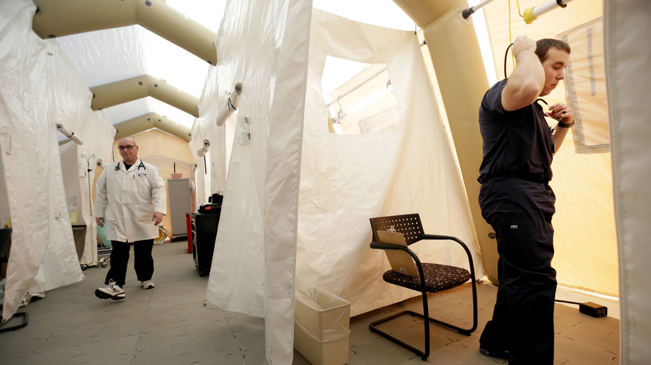 Physician assistants Scott Fillman (left) and Andrew Hunadi get ready to see patients with flu symptoms, in a tent erected just outside the emergency entrance at the Lehigh Valley Hospital in Allentown, Pa. (AP)