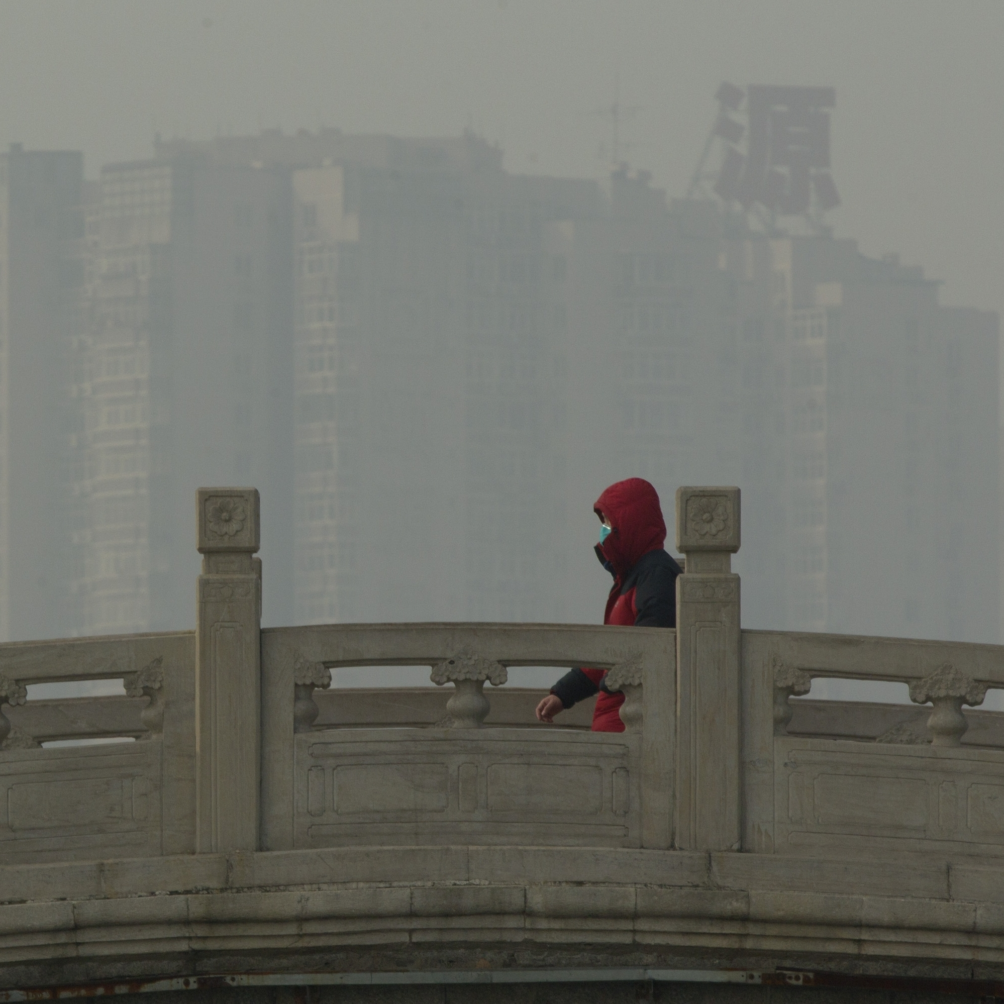 A man wearing a mask walks on a stone bridge in a park on a hazy day in Beijing on Monday. Beijing schools kept children indoors and hospitals saw a spike in respiratory cases following a weekend of off-the-charts pollution in China's smoggy capital, the worst since the government began being more open about air-quality data.