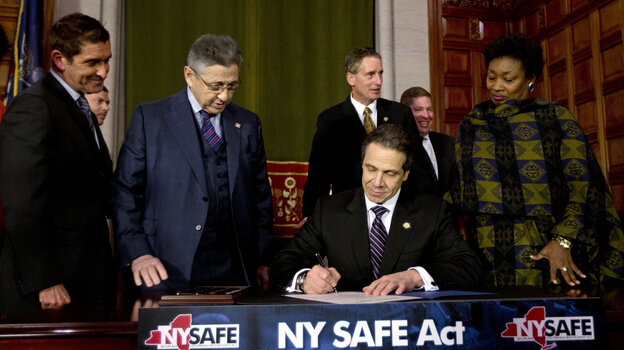 New York Gov. Andrew Cuomo signs New York's new gun-control law Tuesday in Albany, N.Y.
