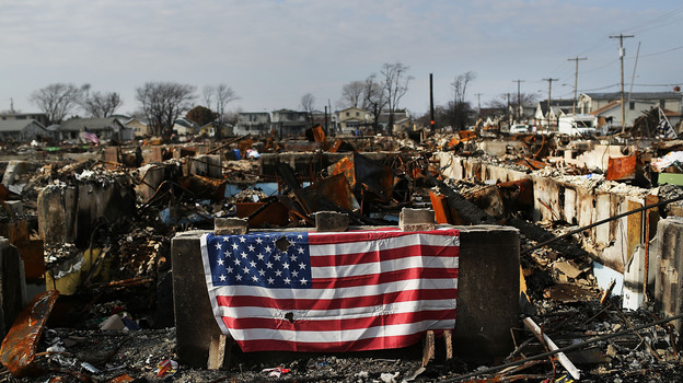 A U.S. flag still hung on the remains of homes in the Breezy Point neighborhood of Queens, N.Y., in December, nearly two months after Superstorm Sandy tore through the area. (Getty Images)