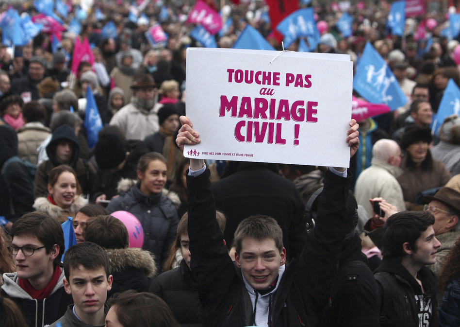 "A boy holds a poster reading ""Do not touch the civil marriage"" during a demonstration in Paris on Sunday as thousands of protesters mobilized against the French president's plan to legalize gay marriage. (AP)"