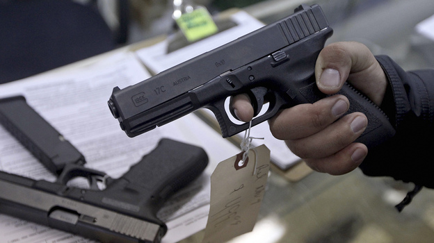 At a gun shop in Phoenix, a  customer holds a handgun. Among the executive actions President Obama is expected to propose is an expansion of background checks for gun buyers. (Reuters /Landov)