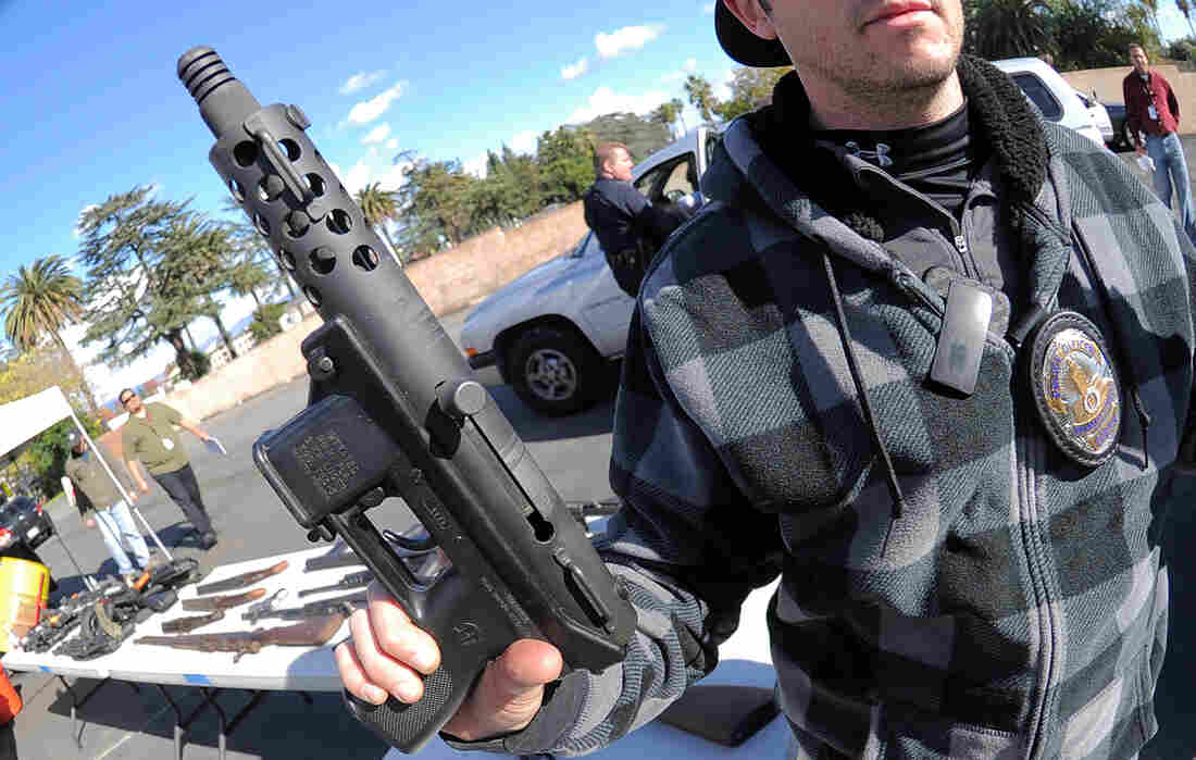 A police officer holds an assault weapon turned in during a gun buyback in the Van Nuys area of north Los Angeles on Dec. 26.