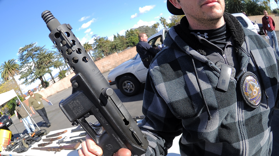 A police officer holds an assault weapon turned in during a gun buyback in the Van Nuys area of north Los Angeles on Dec. 26. (AFP/Getty Images)