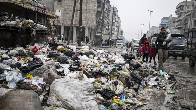 A family crosses a street piled with rubbish in Aleppo, Syria, on Jan. 5. (AP)