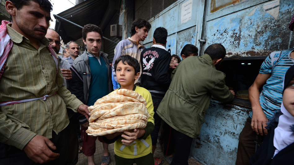 A Syrian boy carries a pile of bread as people crowd outside a bakery in the Salaheddin district of Aleppo, on Oct. 25, 2012. (AFP/Getty Images)