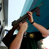 """Los Angeles County Sheriff's Department officer Jay Phillippi looks over a fully automatic Thompson machine gun that was turned in during a """"Gifts for Guns"""" program in Compton, Calif., in 2005."""