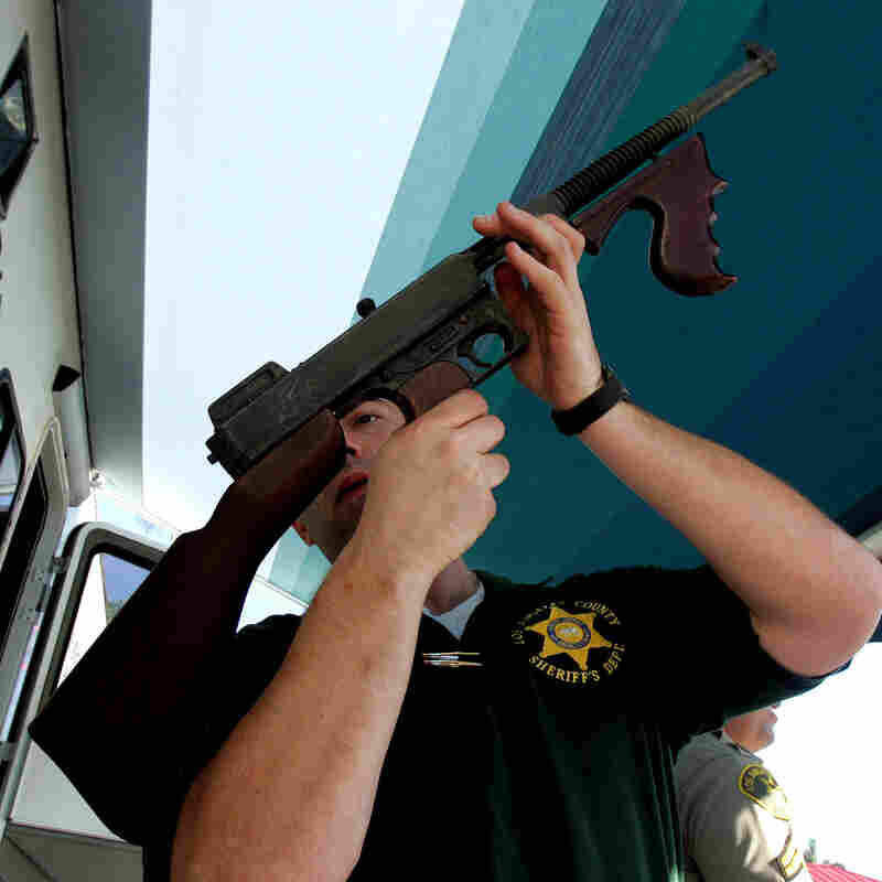 "Los Angeles County Sheriff's Department officer Jay Phillippi looks over a fully automatic Thompson machine gun that was turned in during a ""Gifts for Guns"" program in Compton, Calif., in 2005."