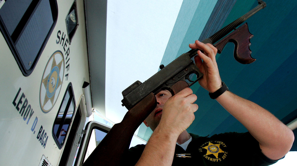 "Los Angeles County Sheriff's Department officer Jay Phillippi looks over a fully automatic Thompson machine gun that was turned in during a ""Gifts for Guns"" program in Compton, Calif., in 2005. (AP)"