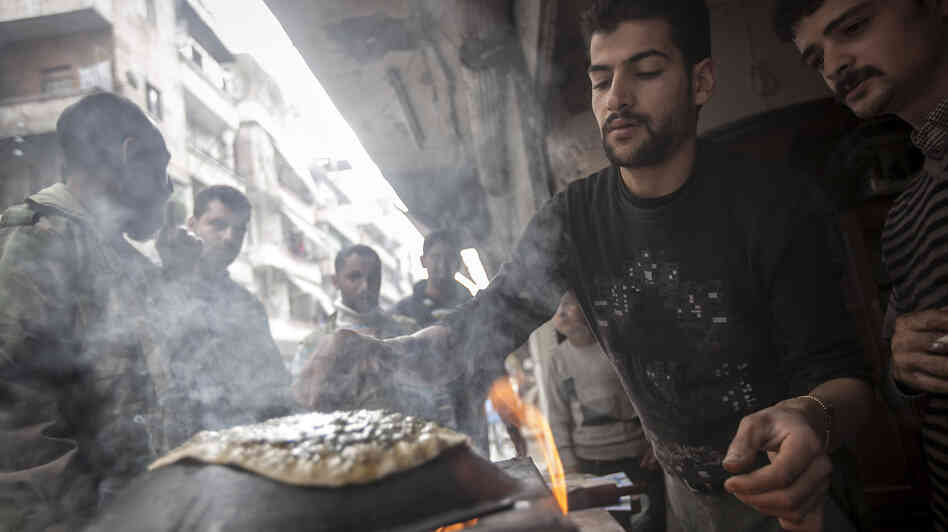 A man makes bread as residents, background, stand in line in front of a bakery during heavy fighting between Free Syrian Army fighters and government forces in Aleppo, Syria, on Dec. 4, 2012.