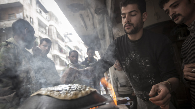 A man makes bread as residents, background, stand in line in front of a bakery during heavy fighting between Free Syrian Army fighters and government forces in Aleppo, Syria, on Dec. 4, 2012. (Associated Press)