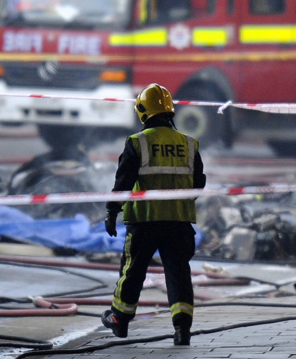A firefighter walks toward some of the wreckage at the scene of today's helicopter crash in London.
