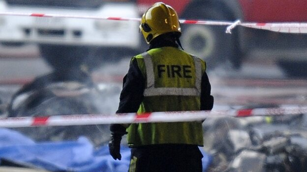A firefighter walks toward some of the wreckage at the scene of today's helicopter crash in London. (EPA /LANDOV)