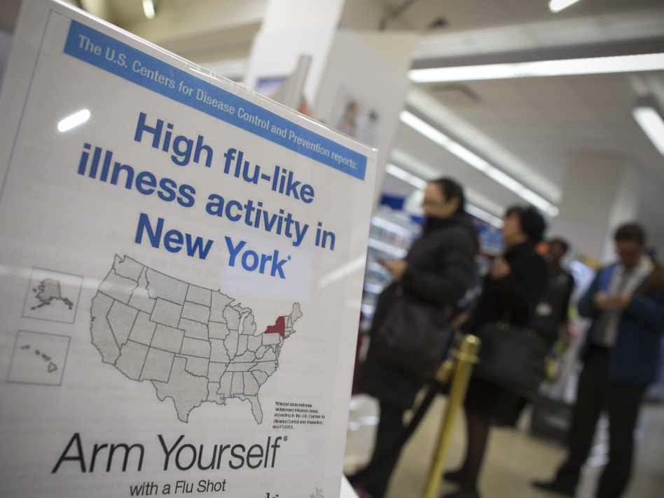 People line up at a Duane Reade pharmacy in New York behind a sign announcing the recent flu outbreak.