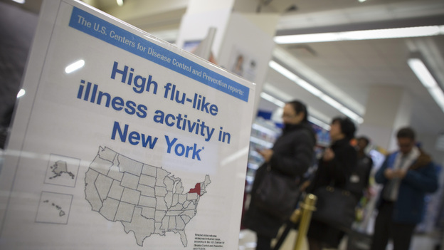 People line up at a Duane Reade pharmacy in New York behind a sign announcing the recent flu outbreak. (Reuters/Landov)