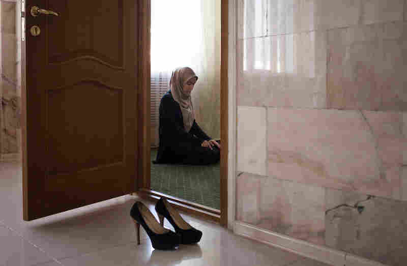 Amina Mutieva, 21, prays before her class at the Islamic University in Grozny.