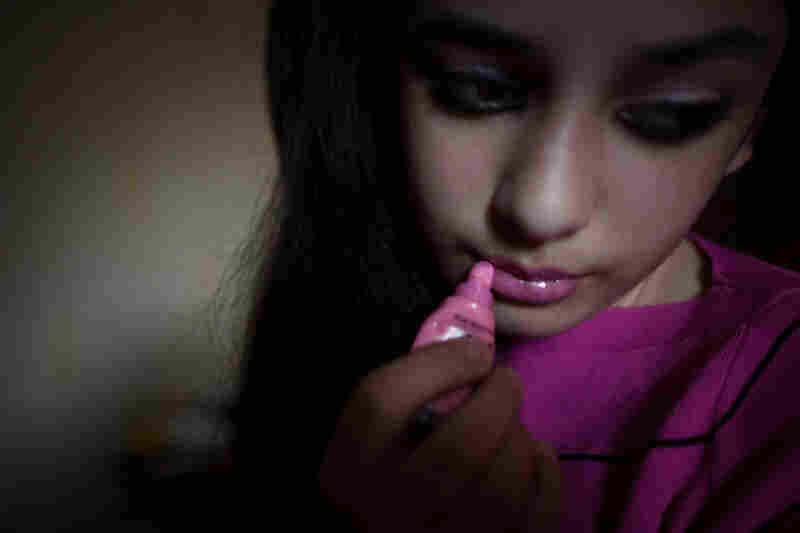 "A Chechen teen, who considers herself ""emo,"" puts on lip gloss in her room. Chechen youth who are influenced by the Western ""emo"" subculture are targets of violence by authorities."