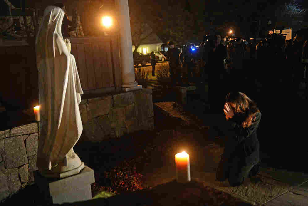 "Aline Marie prays outside St. Rose of Lima church in Newtown, Conn., on the day of the school shooting. She says being photographed made her feel ""like a zoo animal."" The photographer says he tried hard to respect her privacy and grief."