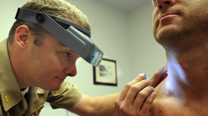 Lt. Cmdr. Stephen Mannino checks a sailor for skin cancer the old-fashioned way during a screening exam at  Naval Amphibious Base Coronado in San Diego.