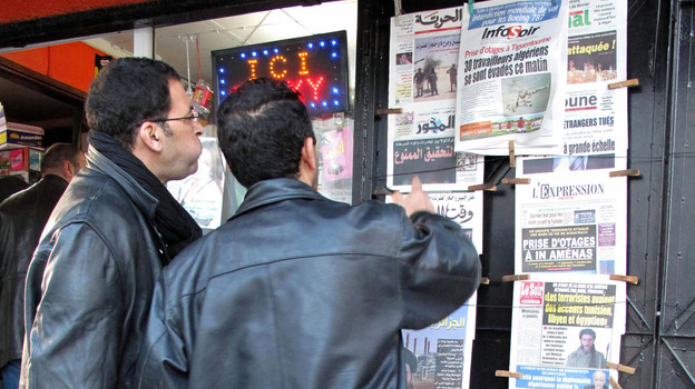 Algerian men look at national newspapers headlining the terrorist attack and kidnapping in Amenas at a news stand in Algiers on Thursday. (AP)