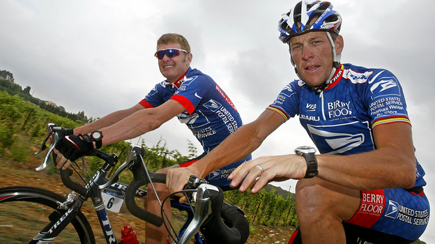 Lance Armstrong, right, faces several court cases tied to evidence that he cheated. One of the suits was filed by his former U.S. Postal Service teammate Floyd Landis. Here, the pair ride during the 2003 Tour de France. (AFP/Getty Images)