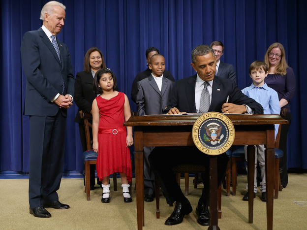 President Obama signs a series of executive orders Wednesday about the administration's gun law proposals as Vice President Biden and children who wrote letters to the White House about gun violence look on.