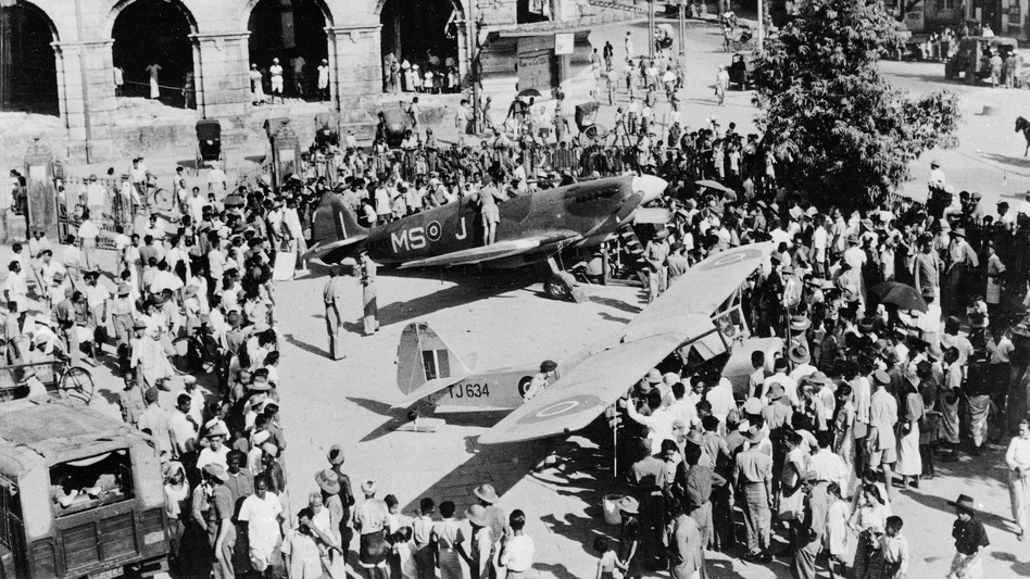 A crowd surrounds a British Spitfire and an Auster in the courtyard of the Civic Hall in Rangoon, Burma, on April 3, 1946. (AP)
