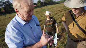 British farmer and businessman David Cundall (left) leads an archaeological excavation team searching for buried World War II Spitfires at an airport in Yangon, Myanmar, Jan. 7. He holds a miniature model of the fighter plane and is accompanied by Tracy Spaight, director of special projects at video game company Wargaming.net, who is funding the effort.