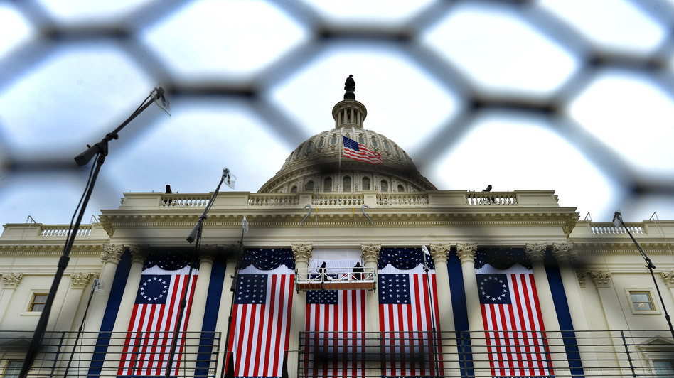 Workers seen through a fence adjust American flags on the Capitol during preparations Thursday for the inauguration. (AFP/Getty Images)