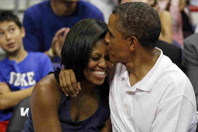 "Aww: Obama sneaks an extra smooch after kissing Michelle for the ""Kiss Cam"" at the basketball game between U.S. and Brazil, on July 16, 2012, in Washington, D.C."