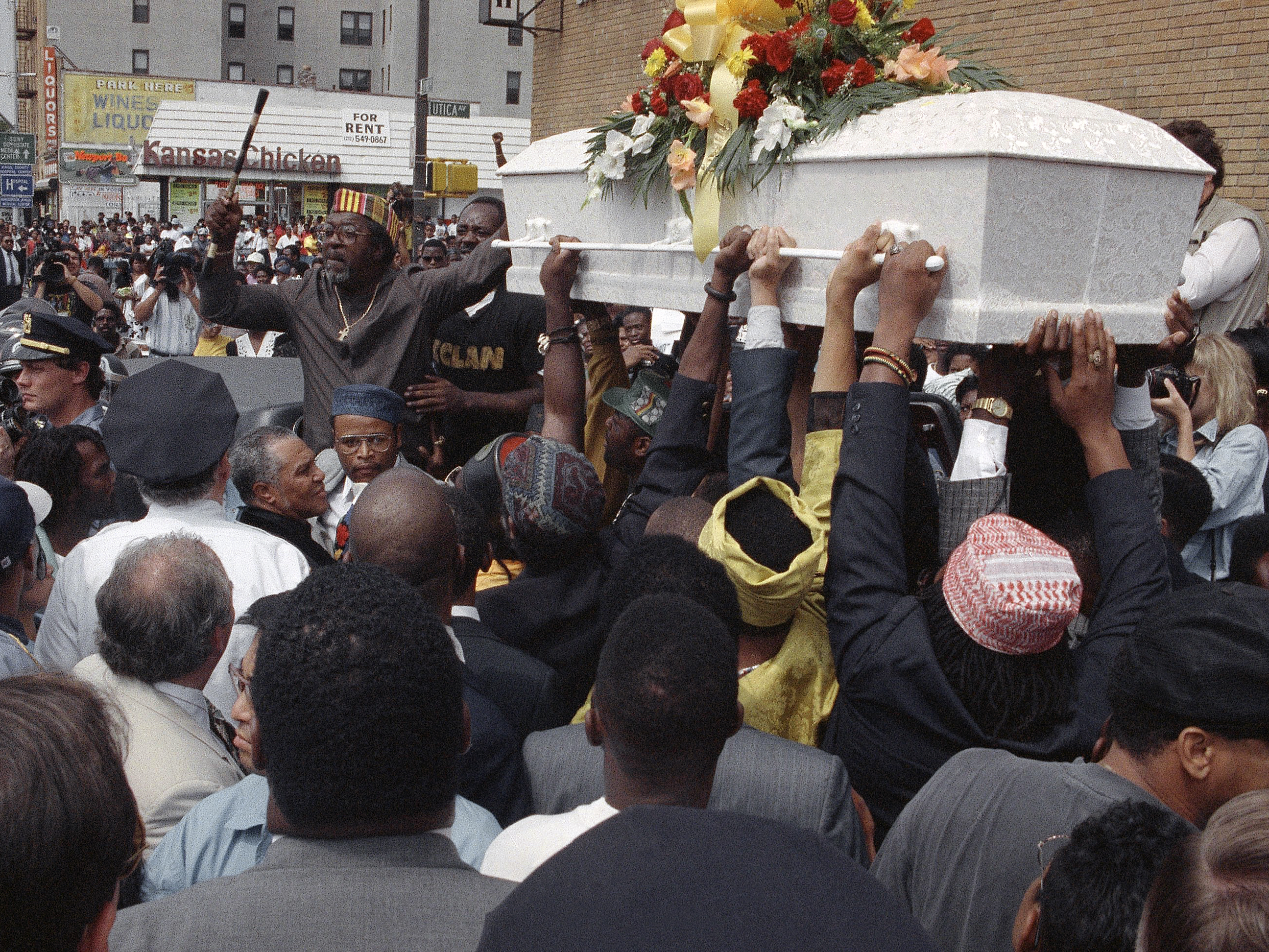 A crowd of mourners gathers outside St. Anthony's Baptist Church in Brooklyn, N.Y., on Aug. 27, 1991 as the casket carrying the body of Gavin Cato passes by.