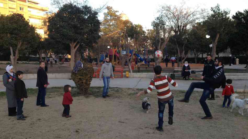 In the Syrian capital, Damascus, many residents try to maintain a normal routine despite the country's war. Here, Damascenes kick a soccer ball in a park.
