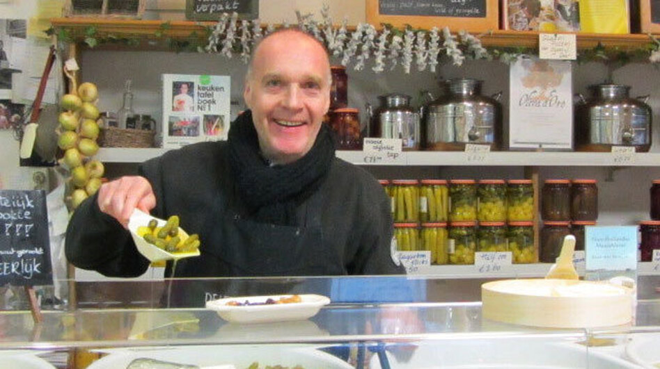Fred Ooms of De Leeuw Zuurwaren, Amsterdam, modeling the traditional method of measuring de Leeuw pickles, the scoop.