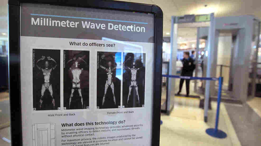 A sign informs travelers about Millimeter Wave Detection technology used in full body scanners at Midway Airport in Chicago. The scanners produce less-revealing images than those that use X-rays.