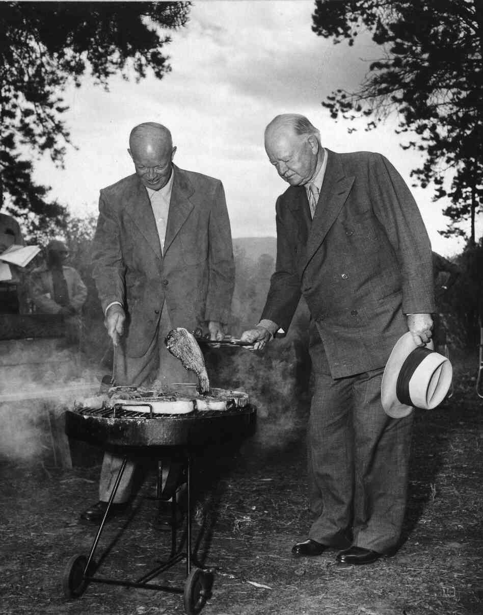 President Eisenhower and former President Herbert Hoover cook steaks on a grill in Fraser, C