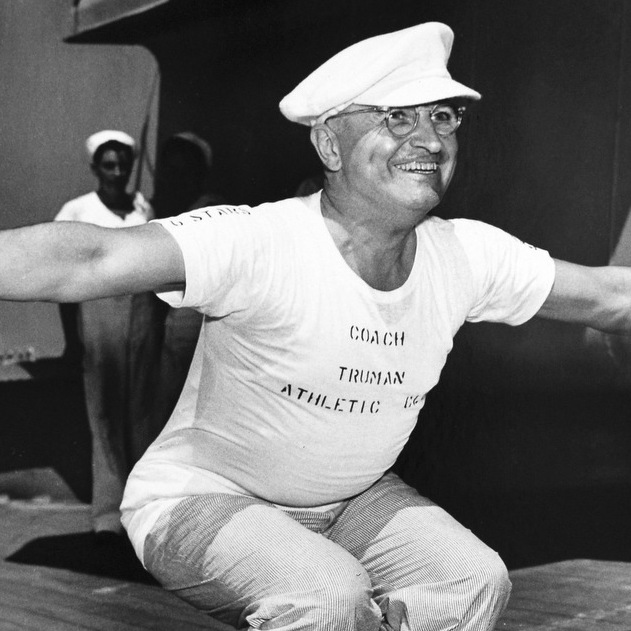 "President Truman, wearing a shirt that reads ""Coach Truman, Athletic Department,"" leads exercises on the deck of the USS Missouri on his return trip to Washington from Brazil, 1947."