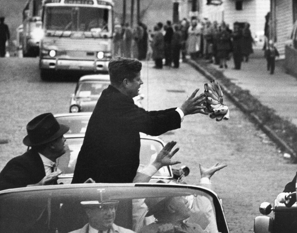 During the 1960 campaign, John F. Kennedy catches a bunch of bananas thrown to him by an admirer.