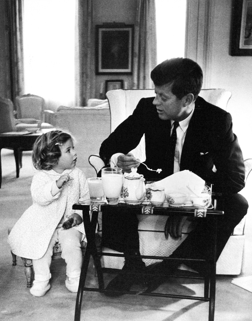 President Kennedy has a breakfast conference with his daughter, Caroline, in the residence area of the White House in 1961.
