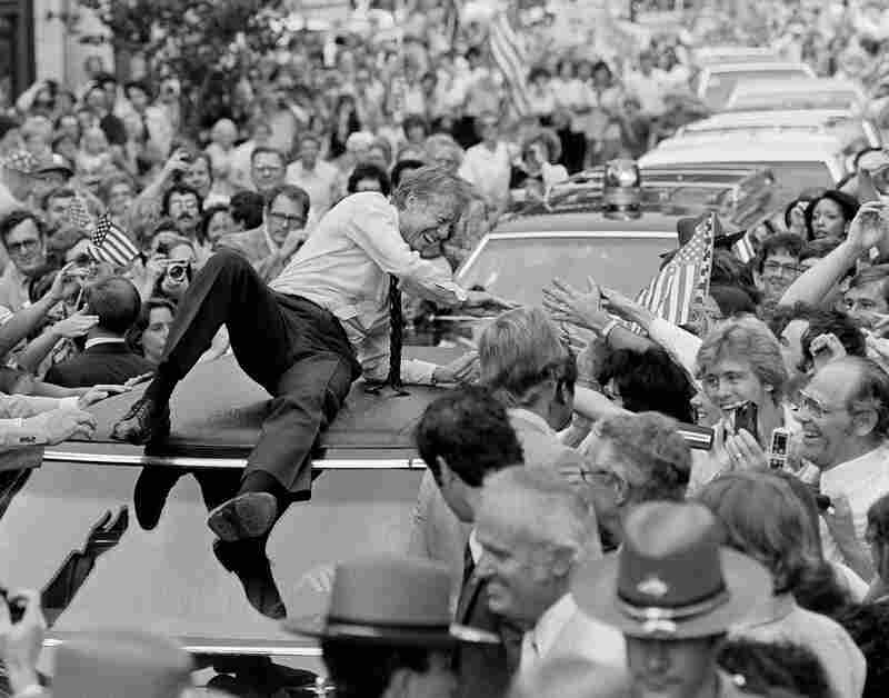 President Carter leans across the roof of his car to shake hands along the parade route on his way to a town meeting in Bardstown, Ky., 1979.
