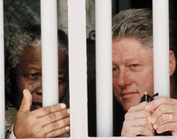 President Clinton and South African President Nelson Mandela peer out of the window of Mandela's former cell on Robben Island outside Cape Town, 1998. Mandela spent 18 of his 27 years as a political prisoner in this cell.