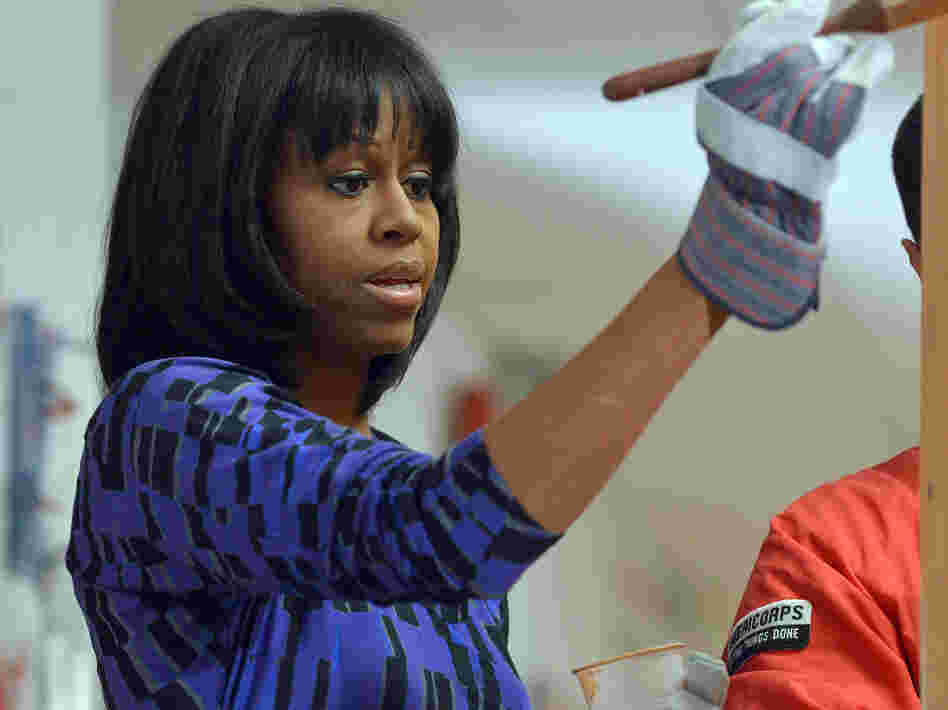 First lady Michelle Obama paints a bookshelf at Burrville Elementary School in Washington, D.C., as part of the National Day of Service on Saturday.